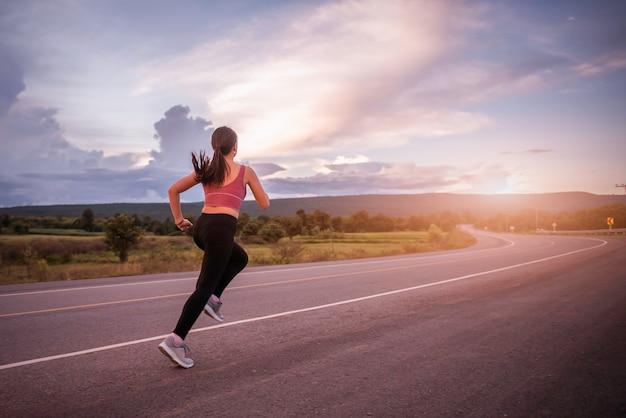 Corridore della giovane donna che corre sulla strada della città con le montagne sullo sfondo.