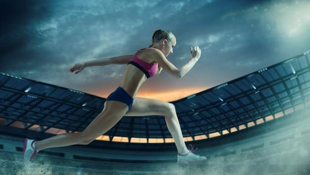 Giovane donna in esecuzione in pista. stadio di atletica leggera notturno illuminato.