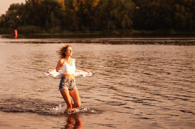 Una giovane donna corre sullo sfondo del fiume e all'alba una bionda sorridente in un top bianco...