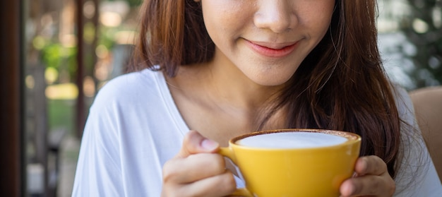 Volto di giovane donna rilassante con latte caldo o caffè durante la mattina. la donna beve il caffè in un bar. buon feeling con il concetto di bere caffè