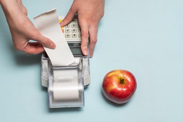 Una giovane donna con le mani in mano strappare un assegno da un registratore di cassa dopo l'acquisto di un prodotto