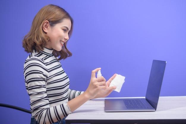 Giovane donna igienizzante spray alcolico con computer, concetto di protezione covid-19.