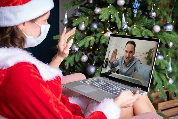 Una giovane donna in costume da babbo natale si siede davanti allo schermo di un computer e agita le mani. auguri di natale on line. capodanno in quarantena. saluto remoto e celebrazione delle vacanze di capodanno.