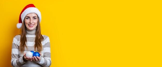 La giovane donna in cappello di babbo natale tiene le palle decorative su uno sfondo giallo. bandiera.