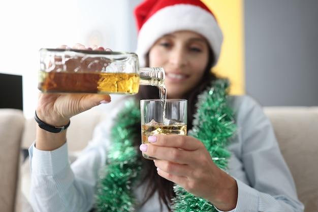 Giovane donna in cappello di babbo natale e orpelli intorno al collo versa l'alcol dalla bottiglia nel bicchiere con ghiaccio