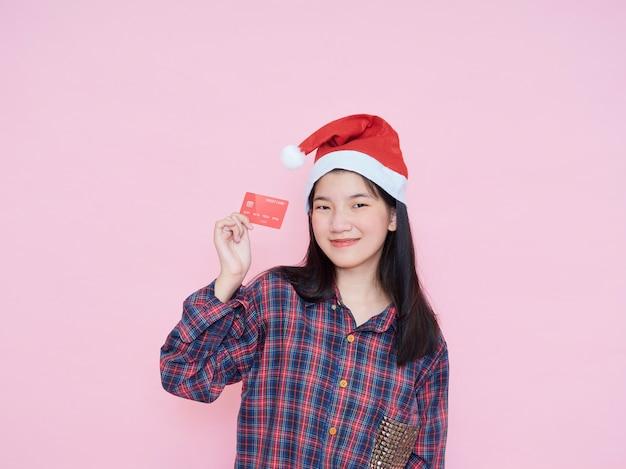 Giovane donna in cappello della santa che tiene la carta di credito sulla parete rosa.