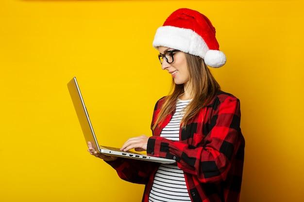 La giovane donna con un cappello da babbo natale e una camicia rossa in una gabbia tiene un computer portatile