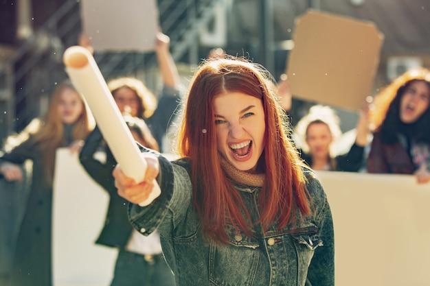 Giovane donna che urla di fronte a persone che protestano per i diritti delle donne e l'uguaglianza per strada. incontro su problemi sul posto di lavoro, pressioni maschili, abusi domestici, molestie. copyspace.