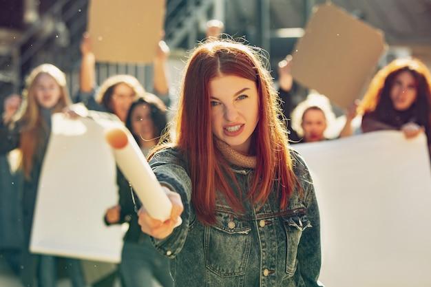 Giovane donna che urla di fronte a persone che protestano per i diritti e l'uguaglianza delle donne