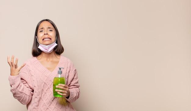Giovane donna che grida con le mani in alto, sentendosi furiosa, frustrata, stressata e sconvolta