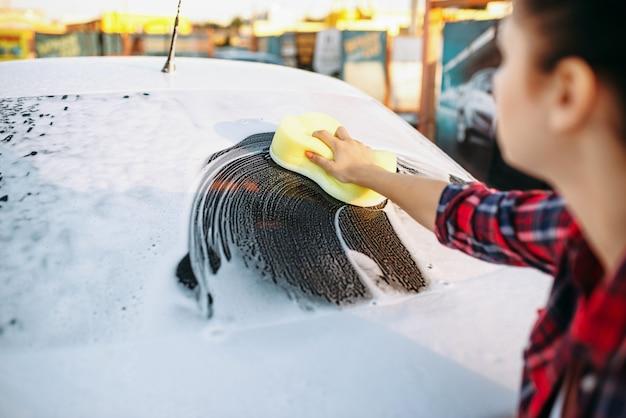 Giovane donna che pulisce il vetro del veicolo con schiuma