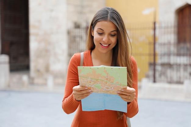 Giovane donna alla ricerca di direzione sulla mappa della città