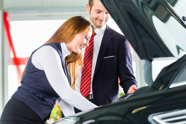 Giovane donna e venditore con auto nel concessionario auto