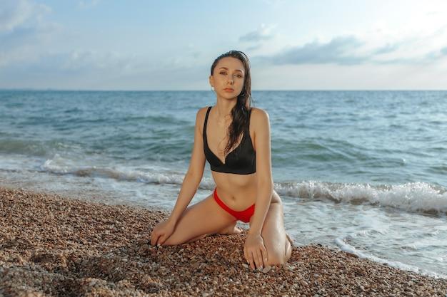 Giovane donna sexy seduta in ginocchio sulla spiaggia