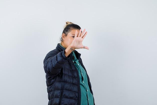 Giovane donna in camicia, piumino che mostra il gesto di arresto e sembra seria, vista frontale.