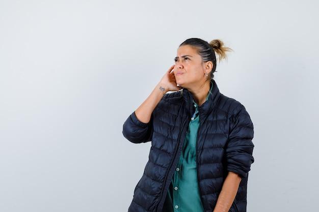 Giovane donna in camicia, piumino con la mano vicino all'orecchio, alzando lo sguardo e guardando confusa, vista frontale.