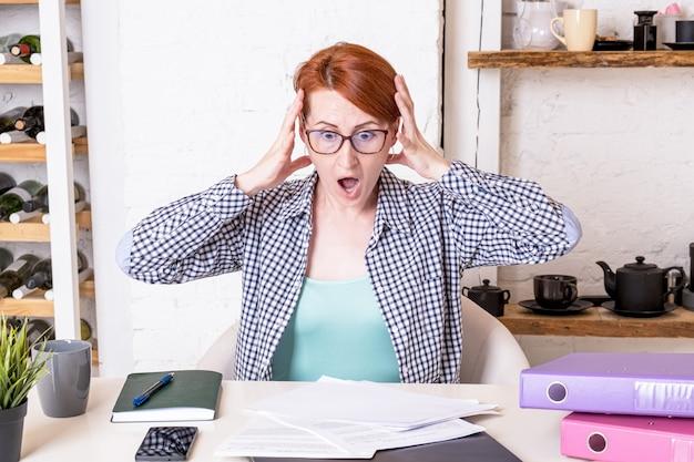 La giovane donna in stato di shock tiene la testa con le mani su una pila di documenti che giace sulla scrivania