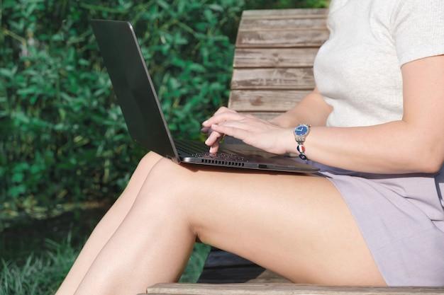 La giovane donna in pantaloncini corti è seduta nel parco su una panchina con un computer portatile in grembo e digita. primo piano delle gambe femminili snelle con un computer portatile. lavoro a distanza, donna d'affari.