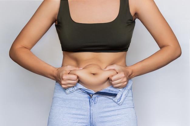 Una giovane donna in un top corto e jeans sbottonati che si tiene per il grasso sulla pancia