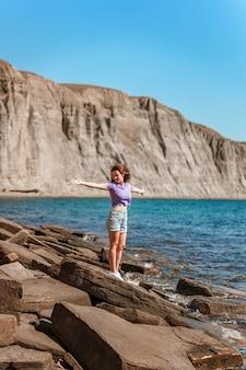 Una giovane donna in pantaloncini corti su una spiaggia rocciosa fatta di pietre naturali in crimea
