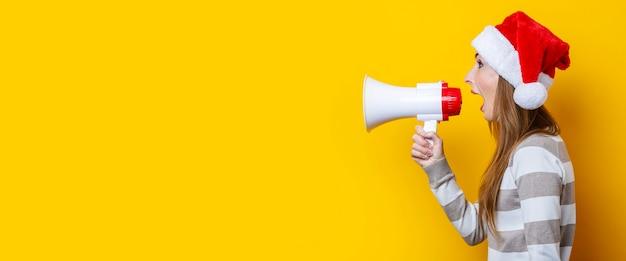 La giovane donna grida in un megafono su uno sfondo giallo. bandiera.