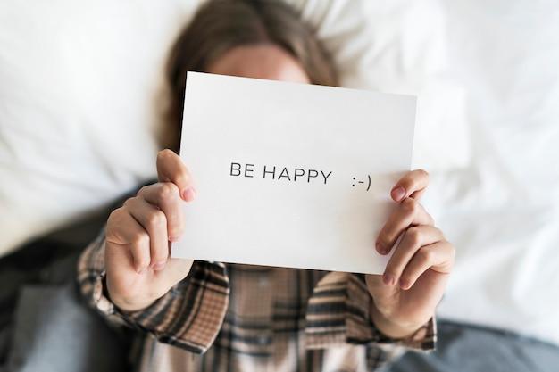 Giovane donna che mostra un biglietto di carta be happy