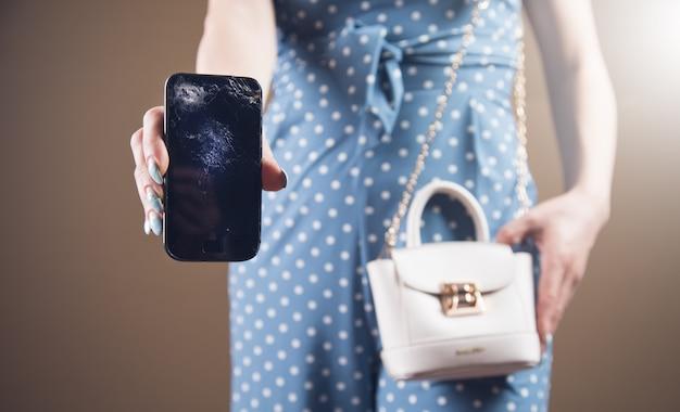 Giovane donna che mostra il telefono rotto