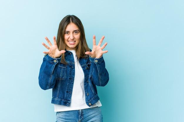 Giovane donna che mostra gli artigli imitando un gatto, gesto aggressivo
