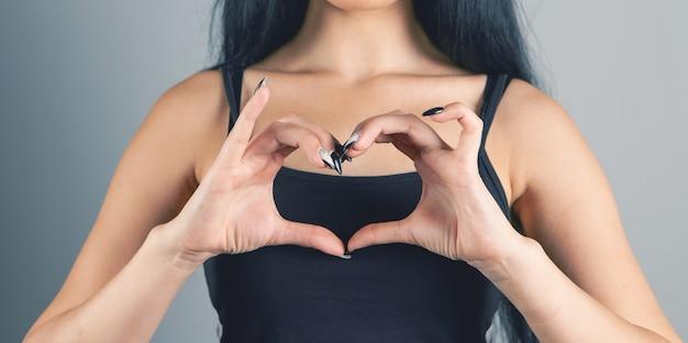 Giovane donna che mostra il cuore su sfondo grigio
