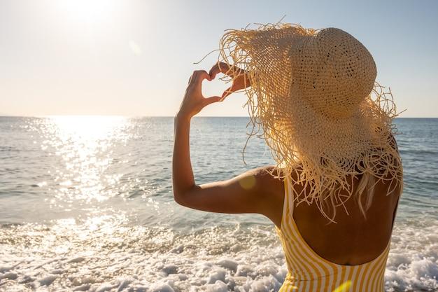 Giovane donna che mostra il simbolo del cuore sulla spiaggia.