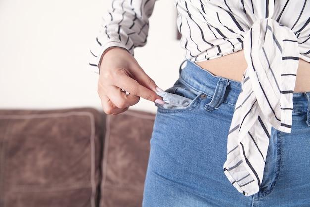 Giovane donna che mostra la sua tasca vuota. senza soldi
