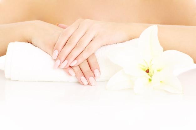Una giovane donna che mostra le mani e la manicure su sfondo bianco