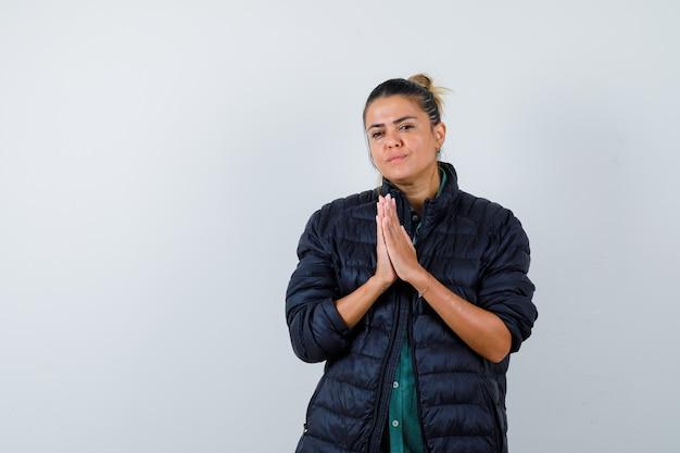 Giovane donna che mostra gesto di namaste in piumino e sembra pensierosa. vista frontale.