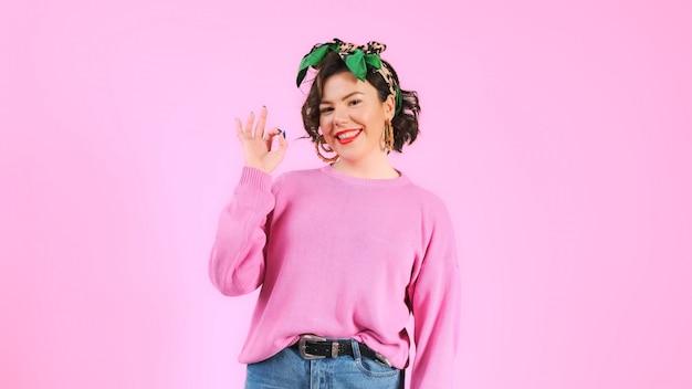 Giovane donna che mostra ok. linguaggio del corpo. sigillo di approvazione va tutto bene. concetto di persone e atteggiamento. gesto.