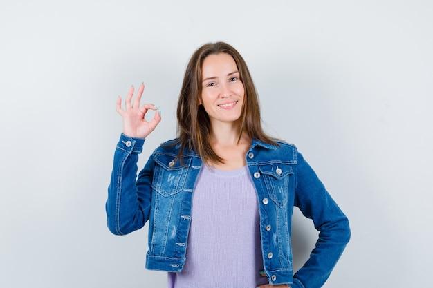 Giovane donna che mostra gesto ok in maglietta, giacca e sembra felice. vista frontale.