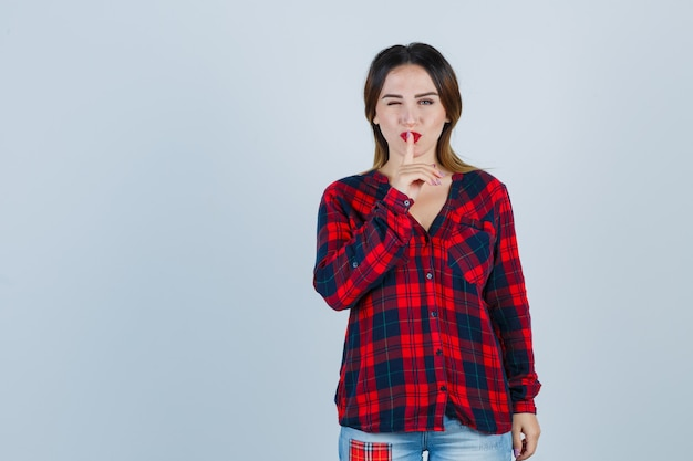 Giovane donna che mostra gesto di silenzio mentre sbatte le palpebre in camicia a quadri e sembra sicura, vista frontale.