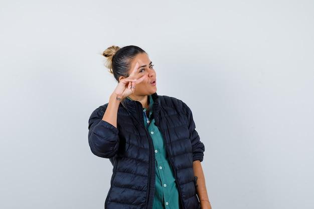 Giovane donna che mostra il segno a v vicino all'occhio in camicia, piumino e sembra fortunata. vista frontale.