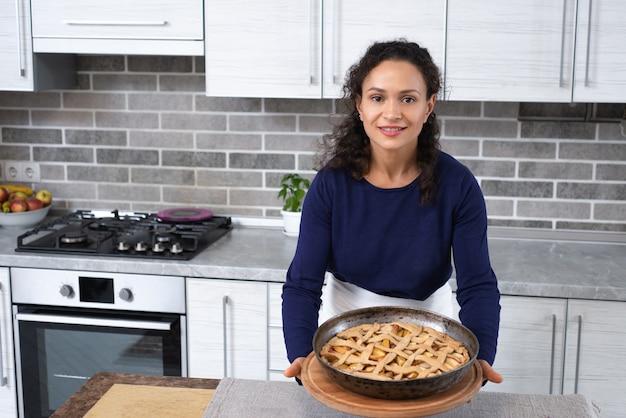 La giovane donna mostra una torta al forno su una tavola di legno