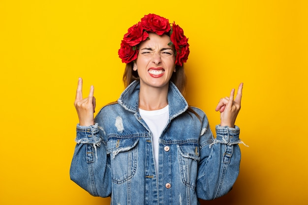 La giovane donna mostra un gesto cool, let's rock this party, in a denim jacket and a crown of red flowers on her head on a yellow wall.
