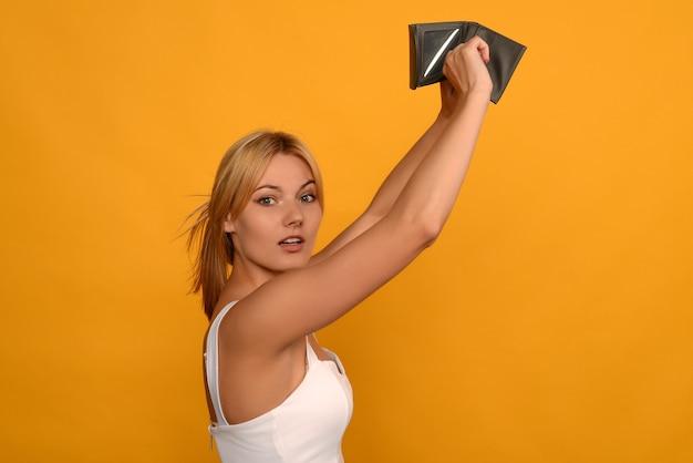 La giovane donna mostra il suo portafoglio vuoto. fallimento
