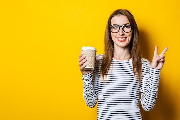 La giovane donna mostra il gesto benvenuto, vetri di pace con una tazza di caffè di carta su fondo giallo