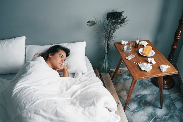 Una giovane donna in un letto malato guarda le sue medicine con la coda dell'occhio