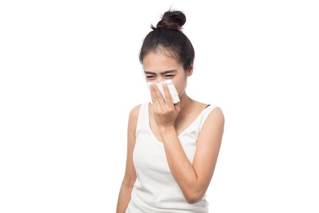 Giovane donna ammalata con allergia e starnuti nel tessuto isolato