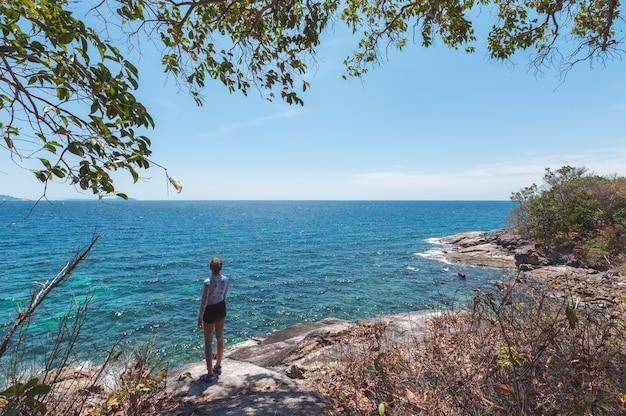 Mare tropicale facente un giro turistico della giovane donna sulla collina della roccia all'isola di lipe