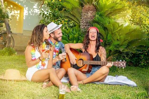 La giovane donna canta e suona la chitarra sull'erba a una festa in giardino