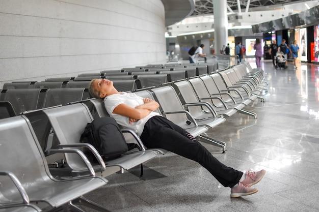 Giovane donna si siede in aeroporto nella sala d'attesa. ritardo del volo