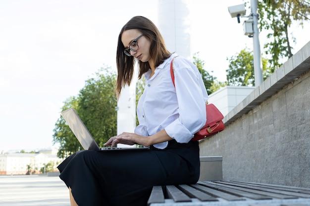 Una giovane donna si siede su una panchina e lavora a un laptop