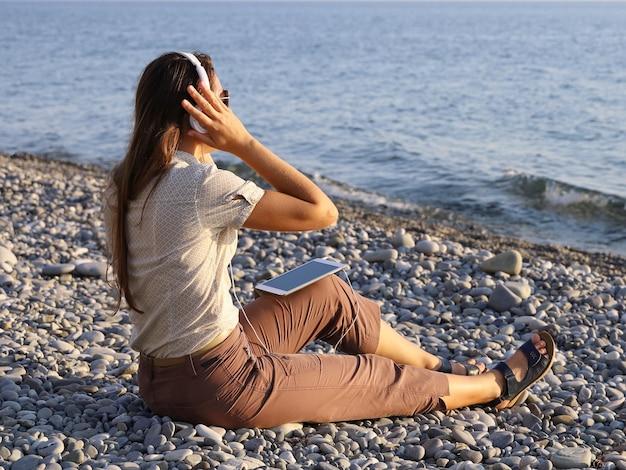 La giovane donna si siede sulla riva di ghiaia deserta e ascolta la musica in cuffia