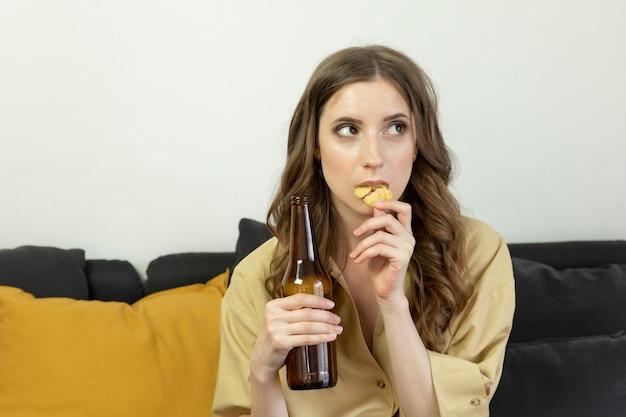 Una giovane donna si siede a casa sul divano e guarda la tv da sola.