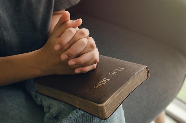 Una giovane donna siede in preghiera per comunicare con dio e la bibbia. religiosi con la preghiera bibbia